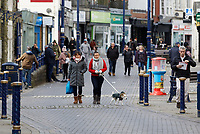 Pictured: People go for a walk, not observing social distancing, in the town sentre of Porthcawl, Wales, UK. <br /> Re: Covid-19 Coronavirus pandemic, UK.