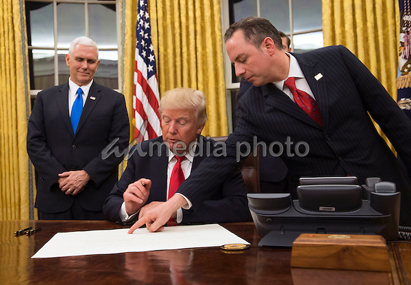 President Donald Trump prepares to sign a confirmation for Defense Secretary James Mattis as his Chief of Staff Reince Priebus points to the order while Vice President Mike Pence watches, at the White House in Washington, D.C. on January 20, 2017. Photo Credit: Kevin Dietsch/CNP/AdMedia