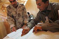 an iraqi official shows the voting sheet to an iraqi soldier from 3d battalion, 1st brigade, 2nd Iraqi Army division before voting in the Iraqi National elections at their base in Camp Ramadi at a pol site under the administration of the Indipendent Electoral Commision of Iraq on Mon Dec 12 2005. At the end of the day about 2000 soldiers will vote at this site according to An Iraqi official.