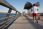Man Jogging on the Harbour Pier Promenade Wall Walk in Alicante, Spain