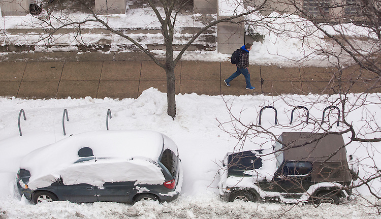 Students make their way down snow covered streets on the Lincoln Park Campus Tuesday, Feb. 3, 2015, following a weekend blizzard that brought double digit snow totals to the city of Chicago. (Photo by Jamie Moncrief)