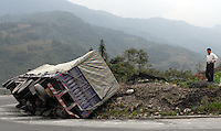 A villager stands next to a truck that was knocked down by the flood caused by the Yaoji Dam. This dam in the mountains of Sichuan near Wolong has flooded a large area displacing many people and their businesses in order to create hydroelectricity for the area. Villagers have demonstrated that they have recieved little compensation and no new homes. The area is close to the famous Wolong Panda reserve..16 Oct 2006