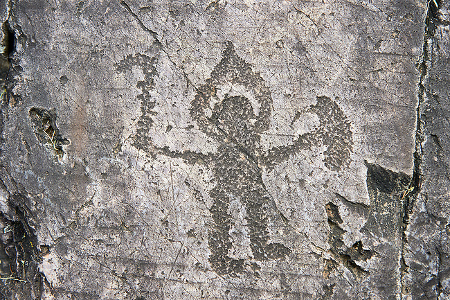 Prehistoric Petroglyph, rock carving, of warrior with a halo type helmet small shield and axe carved by the Camunni people in the iron age between 1000-1600 BC, Seradina I Ronco Felappi Rock 12, Seradina-Bedolina Archaeological Park, Valle Comenica, Lombardy, Italy