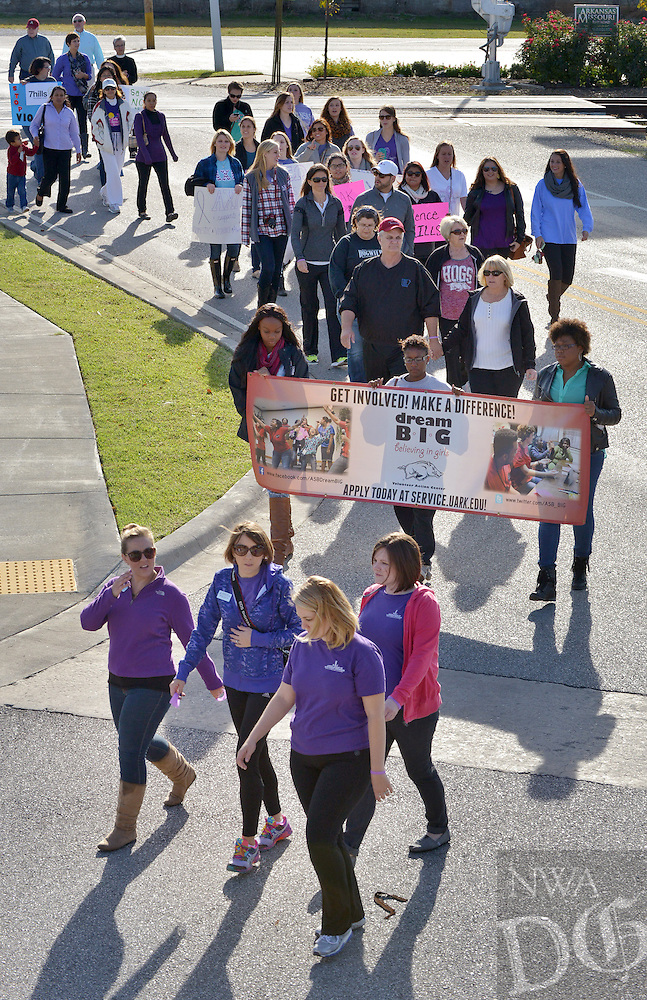 STAFF PHOTO BEN GOFF  @NWABenGoff -- 10/04/14 Participants in the silent vigil walk round the corner of N. Commercial Street and E. Emma Avenue during Peace at Home Family Shelter's Domestic Violence Awareness Month Kickoff event at the Jones Center in Springdale on Saturday October 4, 2015.