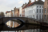 BRUGES, BELGIUM - FEBRUARY 06 : A general view of a canal with bridge on February 06, 2009 in Bruges, West Flanders, Belgium. The reflection of the span and the typical stepped gable roof houses in the water creates a kind of eye under the pedestrian lady crossing the bridge. (Photo by Manuel Cohen)