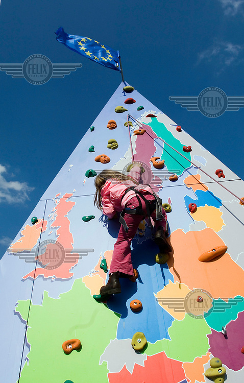 Girl climbing on a map of Europe during an event celebrating the 50th anniversary of the Treaty of Rome, which established the European Economic Community (EEC). The European Union (EU) flag flies at the summit.