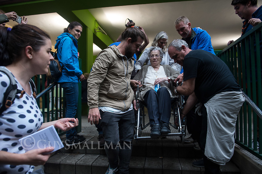Catalan independence vote in Barcelona. The election goes ahead at a polling staion at the 'Ecole Barcelona' School despite the election being declared illegal by the government. 1-10-17Ninety five year old voter Elvira Garcia is assisted and applauded by volunteers at the polling station.