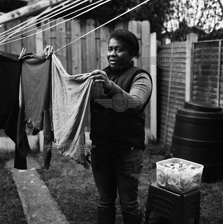 Gorete, a refugee who arrived eleven years ago from Angola, hangs out washing in her garden.