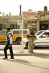 An Iraqi policeman walks past a British Army sentry keeping watch during a security operation in Central Basrah.