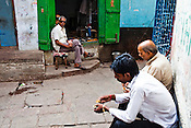 Clients sit to eat snacks in small shop in the ancient city of Varanasi in Uttar Pradesh, India. Photograph: Sanjit Das/Panos