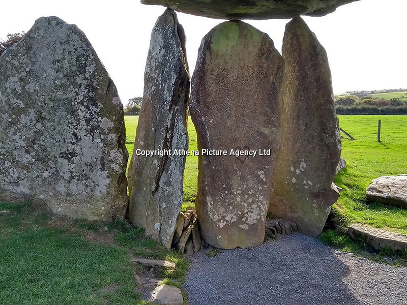 "Pictured: The vandalised ancient monument of Pentre Ifan in Pembrokeshire, Wales, UK<br /> Re: Police, National Park Authority and Cadw officers are investigating damage to a 5,500-year-old monument in Pembrokeshire.<br /> Graffiti has been painted on the Pentre Ifan burial chamber near Nevern, and police are appealing for information to find those responsible.<br /> PC Esther Davies, of the Dyfed-Powys Police rural crime team, said: ""We are saddened by the vandalism to the Pentre Ifan burial chamber. This is one of the most famous prehistoric sites in Wales, and it is unacceptable that someone has done this.<br /> ""Not only have they damaged the monument, but they have caused significant damage to the lichens growing on the stones.<br /> ""Cadw are working closely with us, and will be dealing with the removal of the paint.<br /> ""We would urge anyone who has information about the culprit to contact the Rural Crime team by calling 101.""<br /> Proactive patrols are being carried out by officers, in partnership with Cadw and the Pembrokeshire Coast National Park Authority, at other sites of historic importance to ensure no further damage is caused elsewhere.<br /> Inspector Roger Smith, Heritage Crime Liaison Officer, said: ""We take heritage crime such as this very seriously within Dyfed-Powys.<br /> ""Pentre Ifan is a scheduled ancient monument of immense national and international significance, and we are investigating the damage to it as a priority.<br /> ""We are working closely with our colleagues from both Cadw and the National Park Authority. We are currently piloting a proactive Heritage Watch programme within the National Park, where police officers and PCSOs, together with Cadw wardens and National Park Rangers, are patrolling heritage sites in order to prevent damage and antisocial behaviour."""