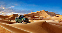 Land Rover Defender amongst the Sahara sand dunes of erg Chebbi, Morocco, Africa