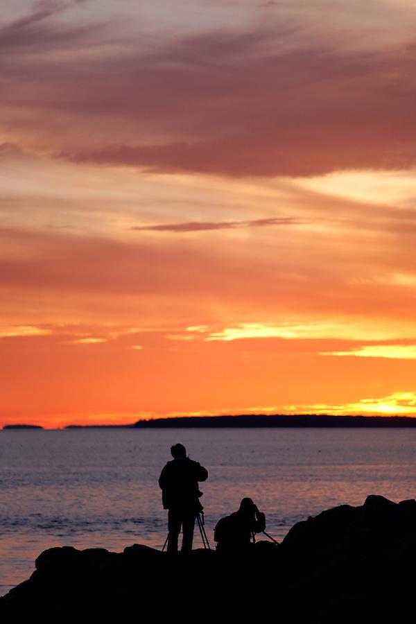 Two photographers photographing sunset over Atlantic Ocean from Bass Harbor Head, Mount Desert Island, Acadia National Park, near Bar Harbor, Maine, USA