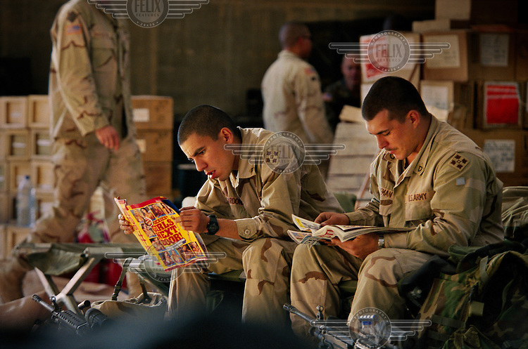 US Infantrymen relax and study soft porn between missions at their forward operating base outside Samarra..In the Sunni triangle with 'Charlie Company', of the 1st Battalion of the 8th Infantry Regiment, 3rd Brigade (based in Fort Carson, Colorado), 4th Infantry Division of the US Army.
