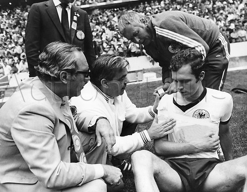 German captain Franz Beckenbauer is treated for a shoulder injury by German team doctor professor Schobert (left) and masseur Erich Deuser (top right) during the 1970 World Cup semifinal Germany against Italy at the Aztec Stadium in Mexico City, Mexico 17 June 1970. Germany lost the game 3-4 against Italy which was scored by Italian midfielder Rivera in the 111th minute. Beckenbauer had sustained the injury to his shoulder at the end of regulation but after a support wrap was applied, he had played on through the two extra time periods of 15 minutes each.