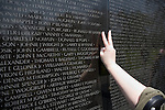 A woman makes the sign for peace before pressing her hand to the surface of a section of the Vietnam war Memorial in the American capitol of Washington D.C.