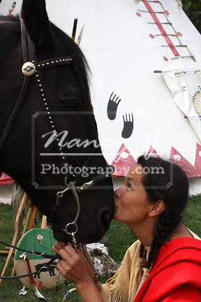 Native American Indian woman kissing her horse