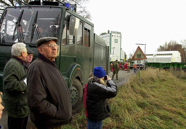 Polizei sichert Castor-Transport<br /> Ein Transport von zwoelf Castoren aus der franzoesichen Wiederaufbereitungsanlage La Hague traf am Mittwoch den 13. November 2002 im Wendland ein. Trotz Blokaden auf den Schienen, gelang es den Zug mit nur wenigen Stunden Verspaetung nach Dannenberg zu bringen. Immer wieder hatten sich Umweltschuetzer auf den Gleisen festgekettet, wurden jedoch von der Polizei geraeumt.<br /> Hier: Anwohner des Orschaft Dahlenburg beobachten die Durchfahrt des Atommuell-Transportes durch ihre Ortschaft. Beamte des Bundesgrenzschutz (BGS) sichern die Transportstrecke.<br /> 13.11.2002, Dahlenburg / Niedersachsen<br /> Copyright: Christian-Ditsch.de<br /> [Inhaltsveraendernde Manipulation des Fotos nur nach ausdruecklicher Genehmigung des Fotografen. Vereinbarungen ueber Abtretung von Persoenlichkeitsrechten/Model Release der abgebildeten Person/Personen liegen nicht vor. NO MODEL RELEASE! Nur fuer Redaktionelle Zwecke. Don't publish without copyright Christian-Ditsch.de, Veroeffentlichung nur mit Fotografennennung, sowie gegen Honorar, MwSt. und Beleg. Konto: I N G - D i B a, IBAN DE58500105175400192269, BIC INGDDEFFXXX, Kontakt: post@christian-ditsch.de<br /> Bei der Bearbeitung der Dateiinformationen darf die Urheberkennzeichnung in den EXIF- und  IPTC-Daten nicht entfernt werden, diese sind in digitalen Medien nach &sect;95c UrhG rechtlich geschuetzt. Der Urhebervermerk wird gemaess &sect;13 UrhG verlangt.]
