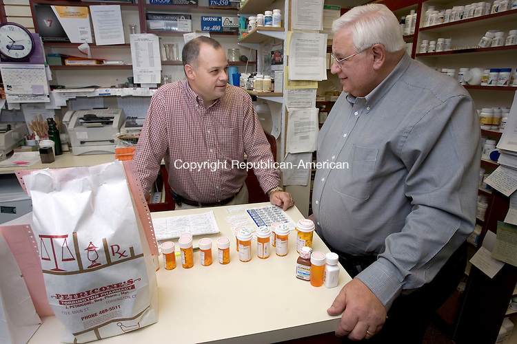 TORRINGTON, CT. 29 December 2010-122910SV04--From left, Joe Petricone Jr. and his dad Joe Petricone Sr. work together behind the prescription counter at their store in Torrington Wednesday. The 80-year-old local drugstore, Petricone's, is planning to expand.<br /> Steven Valenti Republican-American