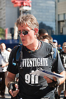 "A protester wearing an ""Investigate 911"" shirt hands out literature at the WTC PATH station."
