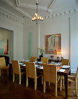 A set of designer chairs surrounds the laid table in the dining room