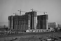 Daytime landscape view from a train of a residential housing complex under construction in Dàtóng Shì Chéng Qū in Shānxī Province, China  © LAN