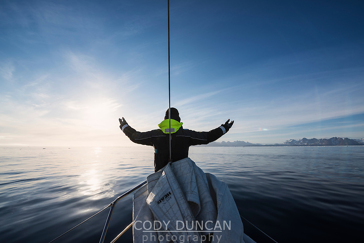 Sailor raises hands towards sun as land approaches off east coast of Greenland