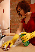 A woman of Filipino origin uses gloves and domestic cleaner such as Fantastik, Ajax, VIM to clean a bathroom sink<br /> (Model Release Photo)<br /> <br /> photo (c) Pierre Roussel -  Images Distribution