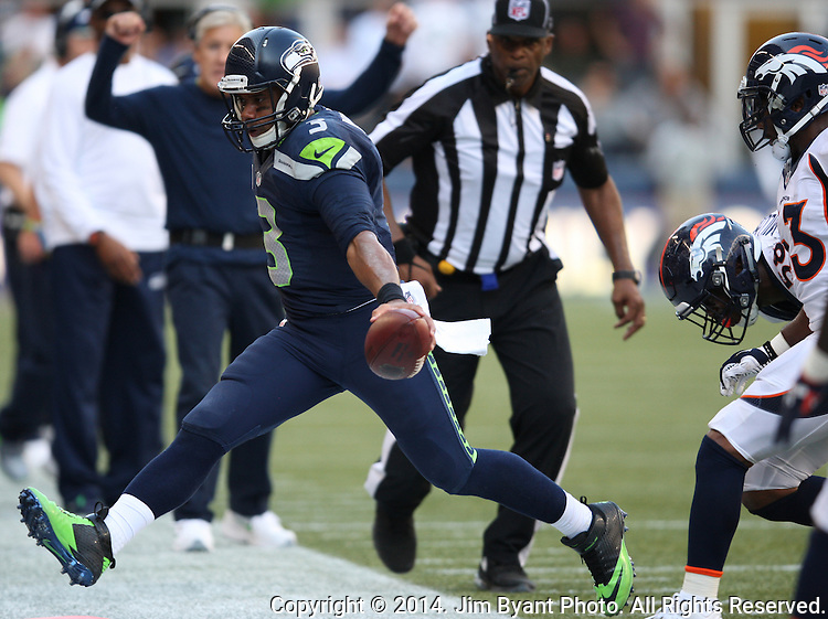 Seattle Seahawks quarter Russell Wilson (3) reaches for a first down as he scrambles away from the Denver Broncos  at CenturyLink Field in Seattle, Washington on September 21, 2014.  Wilson completed 24 of 34 passes for 258 yards, two touchdowns and one interception in the 26-20 overtime win against the Broncos.  ©2014. Jim Bryant Photo. All rights Reserved.