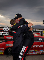 Mar 29, 2014; Las Vegas, NV, USA; NHRA pro stock driver Erica Enders-Stevens (right) celebrates with a crew member after winning the K&N Horsepower Challenger during the Summitracing.com Nationals at The Strip at Las Vegas Motor Speedway. Mandatory Credit: Mark J. Rebilas-USA TODAY Sports