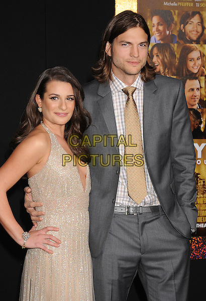"""Lea Michele & Ashton Kutcher.The World Premiere of """"New Year's Eve' held at The Grauman's Chinese Theatre in Hollywood, California, USA..December 5th, 2011.half length gold beige dress low cut plunging neckline cleavage grey gray suit jacket hand on hip.CAP/ROT/TM.©Tony Michaels/Roth Stock/Capital Pictures"""