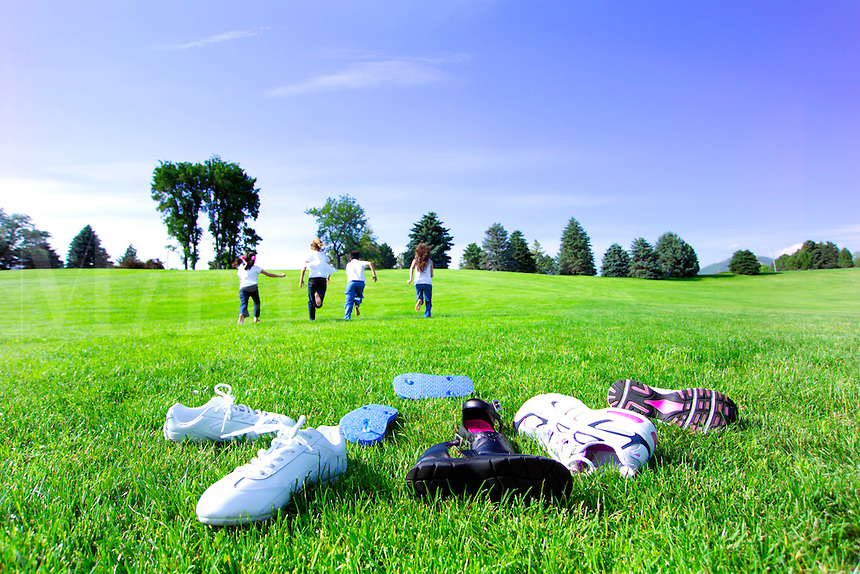 Children with shoes thrown off running through the grass in a park