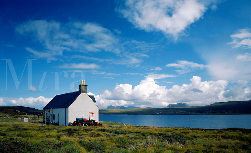 Lonely cottage on the island of Tanera More, The Summer isles, Wester Ross, Scottish Highlands, with the mountains of Assynt in the distance.