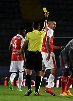 BOGOTA - COLOMBIA - 21 - 03 - 2018: Bismarks Santiago (Izq.), arbitro, muestra tarjeta amarilla a Jose Moya (Der.), jugador de Independiente Santa Fe, durante partido aplazado de la fecha 3 entre Independiente Santa Fe y America de Cali, por la Liga Aguila I 2018, en el estadio Nemesio Camacho El Campin de la ciudad de Bogota. / Bismarks Santiago (L), referee, shows yellow card to Jose Moya (R) player of Independiente Santa Fe, during a posponed match of the 3rd date between Independiente Santa Fe and America de Cali, for the Liga Aguila I 2018 at the Nemesio Camacho El Campin Stadium in Bogota city, Photo: VizzorImage / Luis Ramirez / Staff.