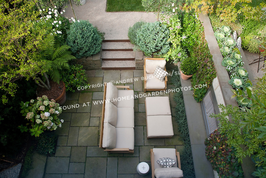 An overhead view of all three levels of this multi-tiered yard: lower fireplace area; middle lawn area, and upper dining area.
