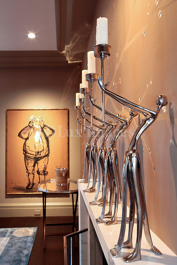 modern silver statuettes holding candles