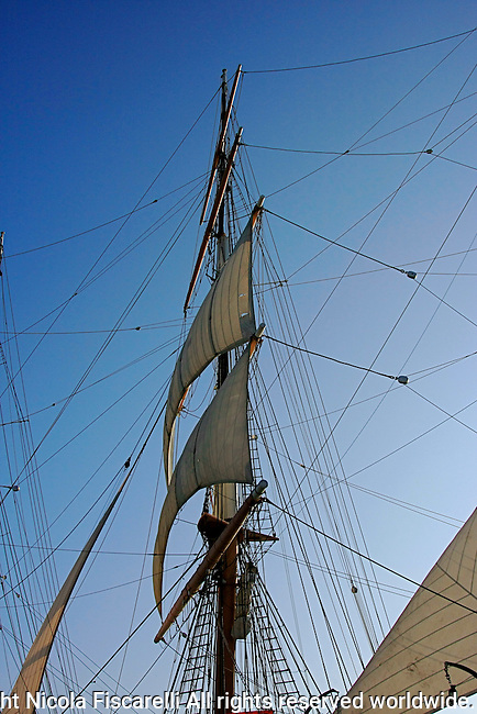 A view of a mast of an old sailboat against the blue sky in San Diego Marina California.