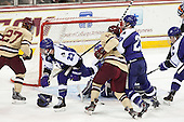 Matt Ginn (HC - 35) loses his glove during a battle for the puck with Quinn Smith (BC - 27), Ryan McGrath (HC - 23), Adam Gilmour (BC - 14), Tommy Dwyer (HC - 20). - The visiting College of the Holy Cross Crusaders defeated the Boston College Eagles 5-4 on Friday, November 29, 2013, at Kelley Rink in Conte Forum in Chestnut Hill, Massachusetts.