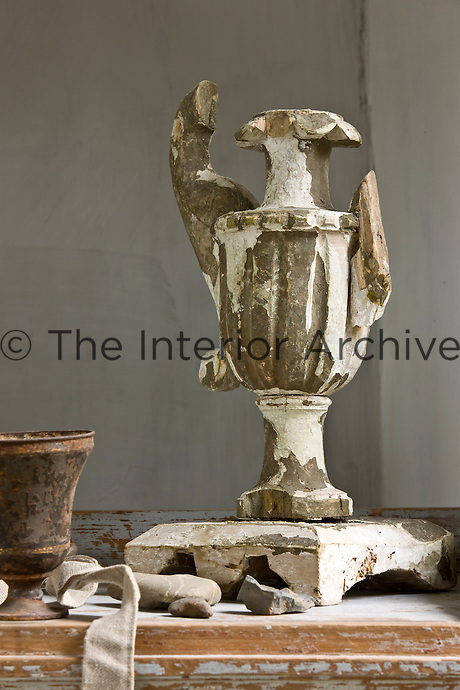 A damaged vase salvaged from an Italian church is displayed on a Gustavian bureau in the salon