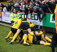 Ricky Holmes of Northampton Town is mobbed after scoring the winning goal to make it 2-3 during the Sky Bet League 2 match between Stevenage and Northampton Town at the Lamex Stadium, Stevenage, England on 19 March 2016. Photo by David Horn / PRiME Media Images.