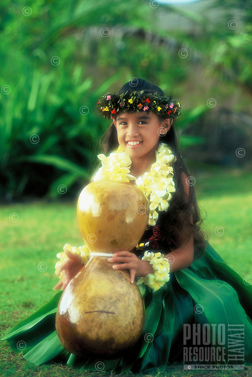 Beautiful young Hawaiian girl (age 7)with ipuheke (gourd), plumeria leis and ti leaf skirt performing a hula noho (seated hula)