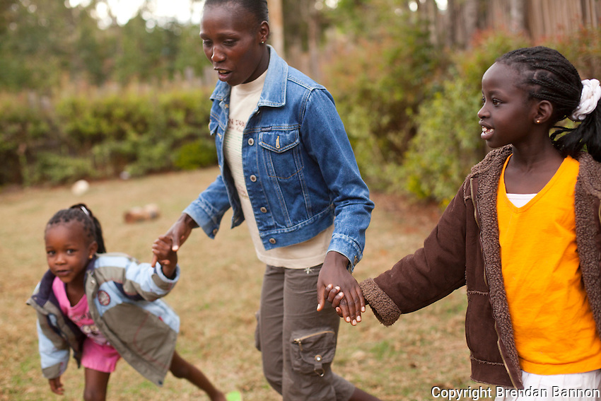 Florence Kiplagat, one of Kenya's leading women marathon runners at home with her daughters Asha and  Faith. Kiplagat trains with coach Renato Canova at high altitude in Iten, Kenya.