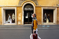 Max Mara's store closed in a desert Via Condotti, with a masked woman passing by<br /> Rome March 12th 2020. Rome the day after the last Coronavirus decree, that increase the restrictions of the march 9th decree. All the shops, bars, restaurants and pubs will have to stay close, apart for the ones of public utility as pharmacies, supermarkets and tobacco stores. People are requested to stay at home and go out just to buy food or medicines. In city centre, police officers warn the few tourists and passers to stay into the hotels or at home and to get out just to find food. <br /> Photo Samantha Zucchi Insidefoto