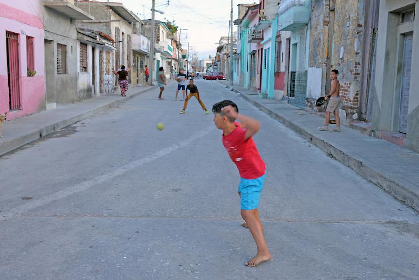 Children play baseball at dusk on a street in Santa Clara, Cuba. MARK TAYLOR GALLERY