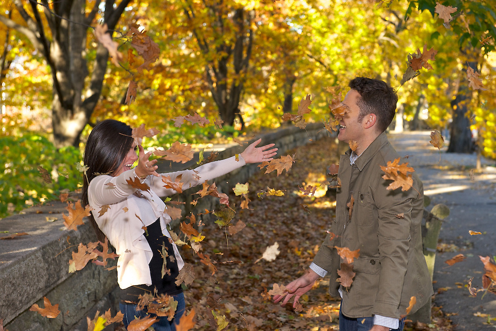 A playful candid from an engagement session in Riverside Park- couple throwing leaves with colorful fall foliage in the background.