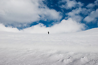 A lone climber in Colorado reaches for the sky on a snow covered peak.