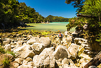 Hikers enter Stilwell Bay on Abel Tasman Coastal Track, Abel Tasman National Park, Nelson Region, New Zealand, NZ