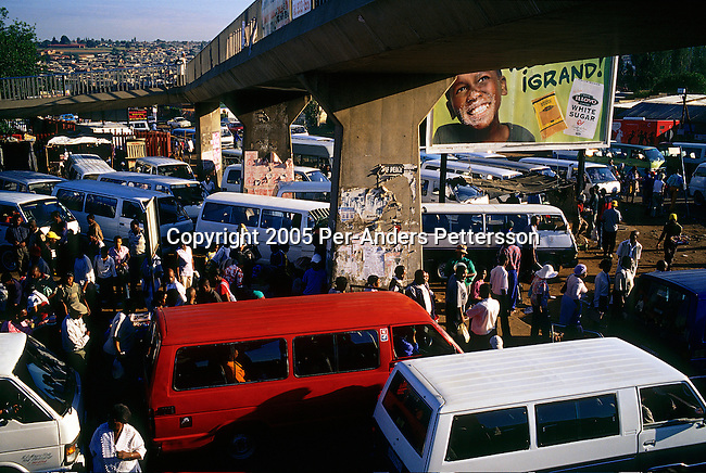 SOWETO, SOUTH AFRICA MARCH 14: Commuters queue for mini bus taxis at Baragwanath taxi station on March 14, 2005 in Soweto, Johannesburg, South Africa. The station is the largest in the township and tens of thousands of people use it every day for travel around Johannesburg. Soweto is South Africa?s largest township and it was founded about one hundred years to make housing available for black people south west of downtown Johannesburg. The estimated population is between 2-3 million. Many key events during the Apartheid struggle unfolded here, and the most known is the student uprisings in June 1976, where thousands of students took to the streets to protest after being forced to study the Afrikaans language at school. Soweto today is a mix of old housing and newly constructed townhouses. A new hungry black middle-class is growing steadily. Many residents work in Johannesburg, but the last years many shopping malls have been built, and people are starting to spend their money in Soweto.  .(Photo by Per-Anders Pettersson/Getty Images)..