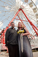 Karri Strong exchanges wedding vows with Joshua Mercer, both of Lehigh Acres, underneath the Ferris Wheel, as one of the winning couples in the annual 'Marriage on the Midway' contest created by Gator Country 101.9, during the 35th annual Collier County Fair in Naples, Florida, USA, March 26, 2011. Photo by Debi Pittman Wilkey