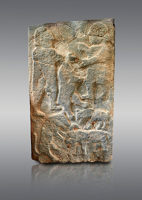 Pictures & images of the North Gate Hittite sculpture stele men hunting. 8th century BC.  Karatepe Aslantas Open-Air Museum (Karatepe-Aslantaş Açık Hava Müzesi), Osmaniye Province, Turkey. Against grey background